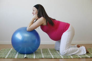 Young pregnant woman doing abdominal muscle exercise.