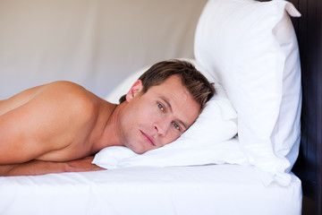 Attractive man relaxing on bed