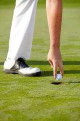 Golfspieler nimmt Ball aus dem hole