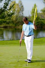 Golfspieler bedient Flaggstock