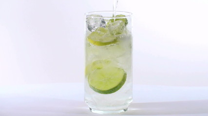 Filling a glass of iced soda with lemon and lime - HD