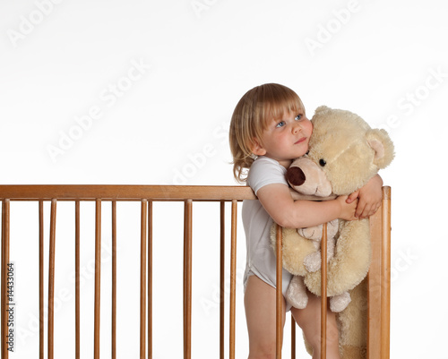 portrait of little girl keeping teddybears in crib