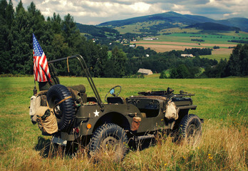 Old fighting jeep Willys in terrain of czech mountains