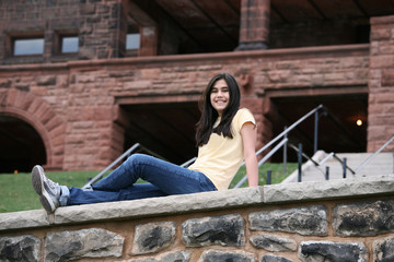 Teen girl sitting on rock ledge