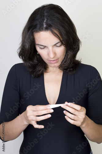 Woman taking temperature or watching a pregnancy test