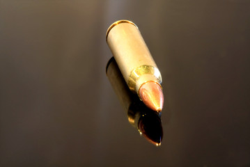 R5 / AK-47 bullet isolated on black reflective surface