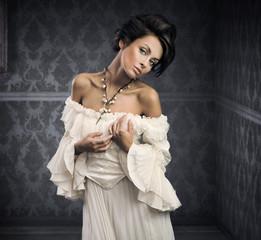 Delicate brunette posing in an vintage room
