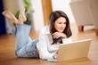 Junge Frau mit Laptop am Boden liegend