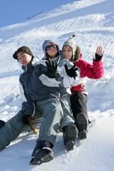 Groupe d'amis assis sur une luge à la neige