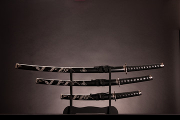 Katana, wakizashi and tanto, monochromatic lighting. Copy space.