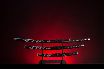 Katana, wakizashi and tanto on red background. Copy space.