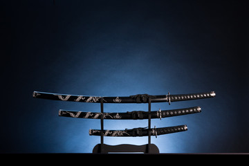 Katana, wakizashi and tanto on blue background. Copy space.