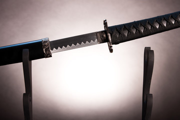 Katana on stand with partially drawn blade,