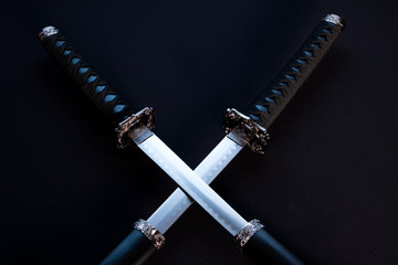 Crossed blades, katana and wakizashi on black background.