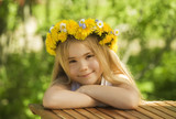 Portrait of a little girl in wreath of flowers