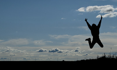 Silhouette of a young joyful man jumping on blue sky background