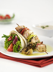 Shish kebab and tortilla filled with vegetable
