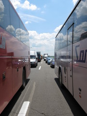 Two Buses on a Highway with Reflecting Sky