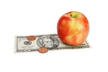 Fresh red apple on twenty dollar bill with coins isolated
