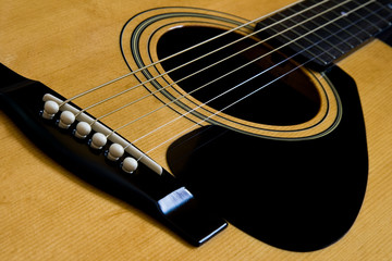 The bridge and strings of and acustic guitar