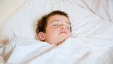 little cute boy asleep in his bed poster
