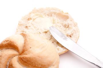 Durchgeschnittene Semmel mit Buttermesser