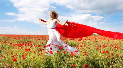 happy woman running with red scarf in poppy field