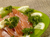 sliced salmon fish on the green plate with greenery and lemon poster