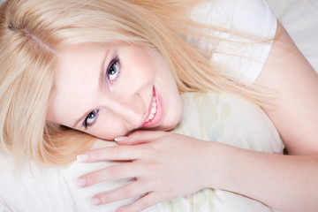 Pretty blond woman with blue eyes on pillow