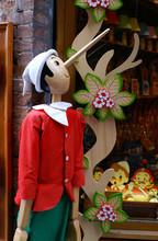 Pinokio Drewniana figura w rozmiarze dziecięcym przed sklepie z zabawkami