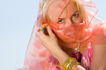 a woman cover her face with a pink dress close-up
