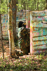 Paintball gamer, soldier aiming and shooting from barier