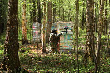 Paintball gamer, soldier aiming and shooting in woods