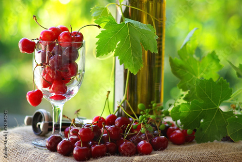 Bottle and glass of white wine and cherries.