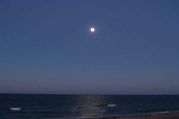 Timelapse clip of the moon rising above a calm ocean