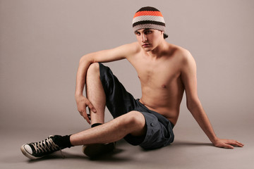 Young man in knitted cap, shorts and gym-shoes