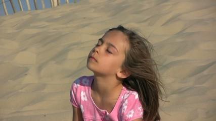 yeux fermés les cheveux au vent sur la dune