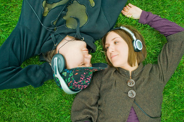 Young couple listening music on grass
