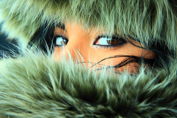 Pretty young woman with a fur hood. Close-up eyes.