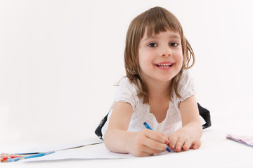 Smiling little girl draws a picture.