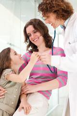 Mature doctor examining happy child, smiling.