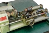 Small portable metal lathe on green board isolated closeup poster