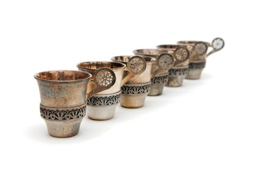 Row of six vintage silver cups isolated