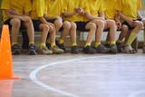 Fototapety Children's feet in sports hall, sit on bench