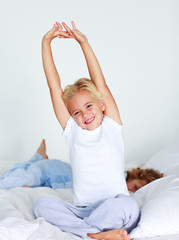 Young child stretching after sleeping
