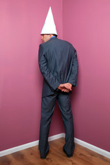 Businessman standing in the corner in a dunce hat