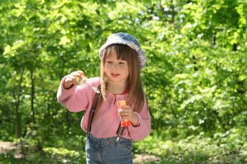 Little girl makes soap bubbles