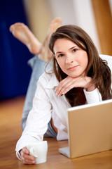 Frau mit Laptop am Boden Blick in die Kamera