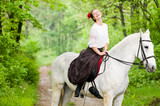 Laughing girl riding horse