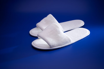 White slippers on blue background